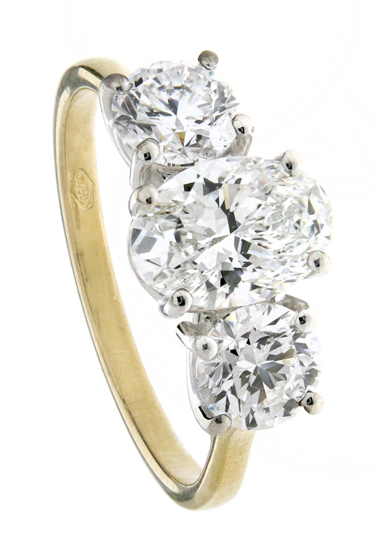 Trilogy Engagement ring with centre oval cut diamond and side round brilliant in yellow gold 18k.